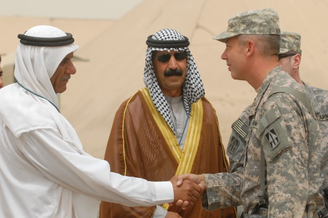 76th Infantry Brigade Combat Team Deputy Commander Col. Kenneth Newlin meets with local leader Sheikh Shehab Ahmed Saleh Al-Tamimi June 17 during the opening of a service center built by local Iraqis and members of the 76th IBCT at Joint Base Balad, Iraq.