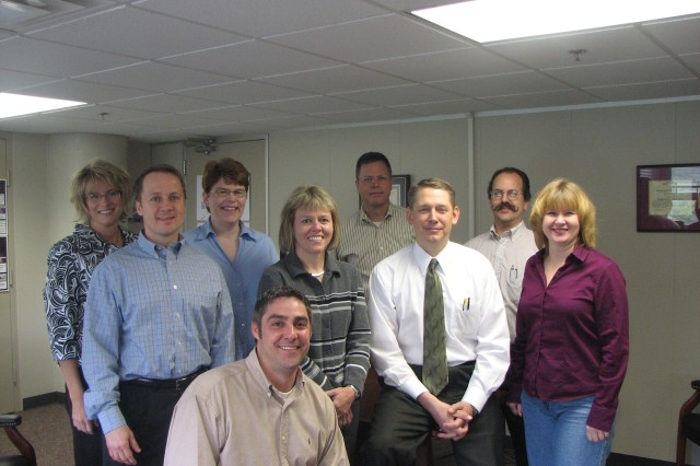 Walt Songaila (third from right),executive director for the Joint Munitions Command Lean Six Sigma office, has a team of supporters to complete the mission. From left: Mary Rus, master black belt candidate; Matt Vilmont, black belt; Kathy Linderman, training coordinator; Cindy Medinger; MBB candidate; Scot Johnson, black belt; Songaila; Steve Tutt, MBB candidate; Christine Werkheiser, secretary. In front, kneeling, Chad DeWitte, financial representative for the JMC LSS office.