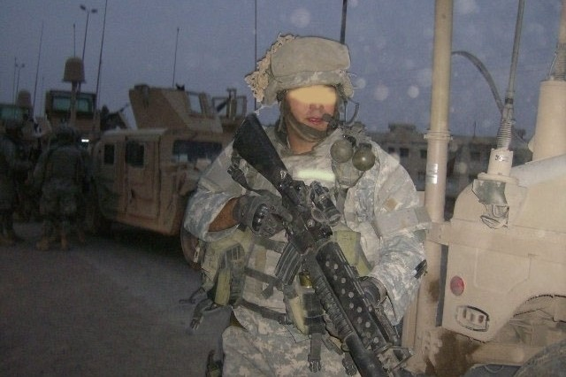 A Soldier on patrol with taped grenades to his uniform.