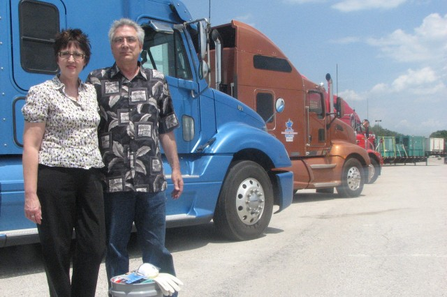 Jeff and Susan McMahon stand in front of several FEMA trucks on the Rock Island Arsenal, Ill. The couple is soliciting volunteers in helping residents affected by this year flooding in Iowa and Illinois.