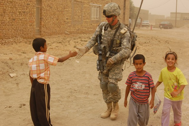 "Pvt. Jesse Huckleberry greets a child while on patrol in the Taji Qada area of northwest Baghdad, June 18, 2008. Huckleberry is with Company B, 1st Battalion, 27th Infantry Regiment ""Wolfhounds,"" 2nd Stryker Brigade Combat Team, 25th Infantry"