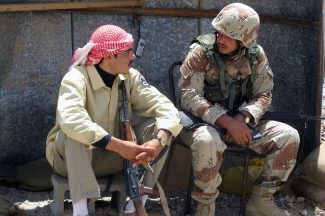 A soldier from the 2nd Battalion, 31st Brigade, 8th Iraqi Army Division, talks with a Sons of Iraq member during Operation Gunslinger Prowl I, a combined Iraqi and Multi-National Division - Baghdad mission focused at ridding the Taji Qada, northwest of Baghdad, of illegal weapons and improvised-explosive devices June 19. The Iraqi army, now nearly 180,000 soldiers, has grown 60 percent in the last year.  The army is growing in both capacity and capability.