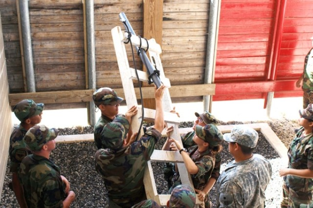 Cadets strategically place their ladder and try to escape the enemy's threshold during the Leadership Reaction Course at Camp Bullis. The mission for the cadets is to get across the wall without sounding the enemy's alarm, a difficult task that requires teamwork and effort.