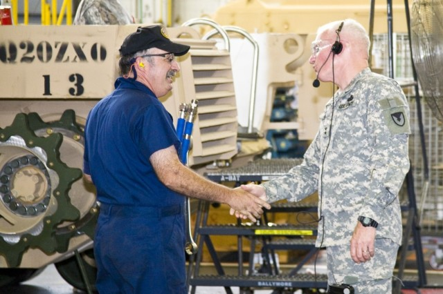 TACOM LCMC's commanding general, Maj. Gen. Scott West, examines the overhaul of combat vehicles inside the 5-acre Stanley Maintenance Facility in the depot's Nichols Industrial Complex. Here, he greets a depot mechanic.
