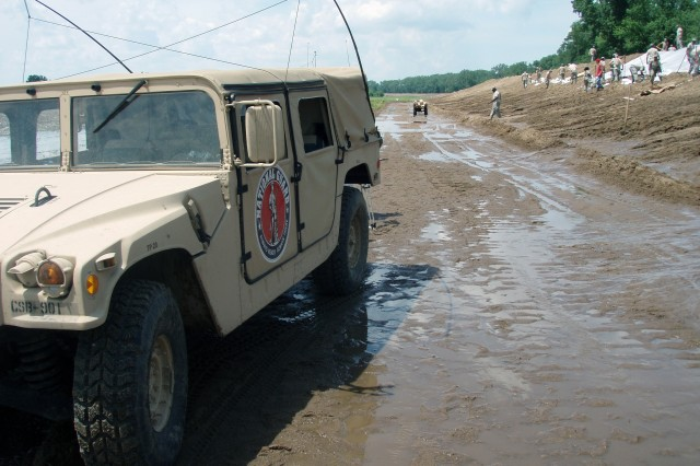 A Missouri National Guard Humvee delivers supplies to Guardmembers working behind it to preserve a Hannibal, Mo., levee June 22.