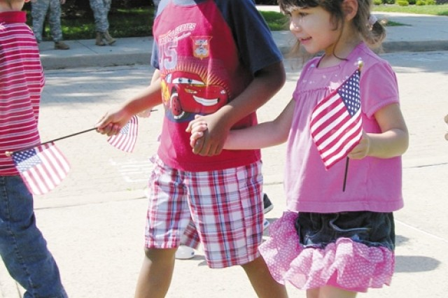 Javon Chamers and Kayla Robinson hold hands and wave American flags during the Aberdeen Area Child Development Center's Army Birthday parade June 12.