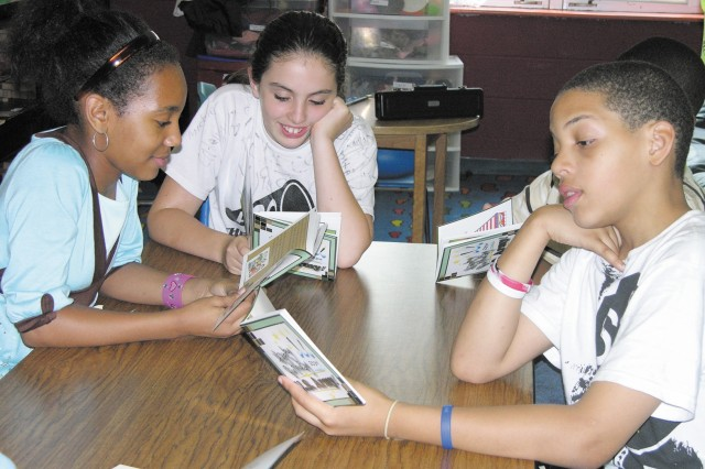 At the Edgewood Area Youth Center, from left, Tatyana Moon, Elise Stole and Kareem Johnson take turns reading the Army Birthday book aloud, one of several activities held during the week to celebrate the Army's 233rd birthday.
