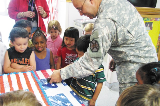 From left Jordon Taylor, 4; Leah Dah, 4; Anya Chervak, 4; and Grace Mitchell, 4, observe Nathan Hoang, 4, and Aberdeen Proving Ground Garrison Command Sgt. Maj. Pedro Rodriguez cut the cake during the Edgewood Area Child Development Center's Army Birthday June 10.