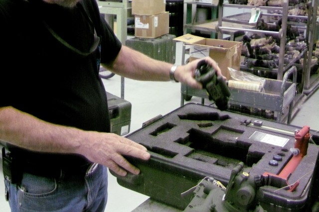 Depot electronics mechanic Rusty Watts removes components from the fire control site box. The components are being repaired by Anniston Army Depot for the 10th Mountain Division (Light Infantry), from Fort Drum, N.Y.