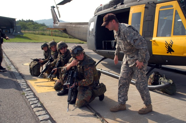 """Staff Sgt. David Miller, Aviation Detachment """"Falcon Team"""" Observer/Controller, conducts pre-flight safety instruction with a group of German Soldiers during U.S.-German Army Partnership Air Assault training at the Joint Multinational Readiness Center in Hohenfels, Germany June 25, 2008"""