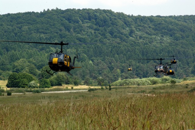 """German Soldiers participating in U.S.-German Army partnership air assault training dismount Aviation Detachment """"Falcon Team"""" Observer/Controller UH-1 aircraft at the Joint Multinational Readiness Center in Hohenfels, Germany on June 25, 2008."""