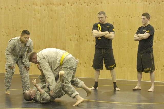 Sgt. 1st Class Carl Lawler and Sgt. Brian Stegemoller watch as students in the Combatives Level II run their own tournament during a recent class.