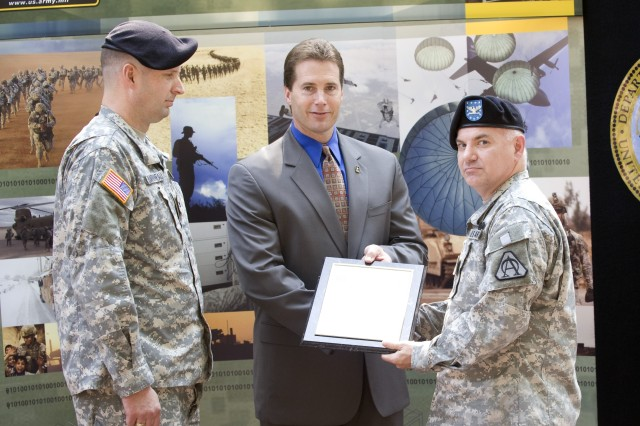 As outgoing Project Manager, Col. James Barrineau looks on, Program Executive Officer for Enterprise Information Systems, Mr. Gary Winkler hands the new Army Knowledge Online/Defense Knowledge Online Project Offices operating charter to Col. Earl Noble, incoming project manager during a June 27 ceremony held at Fort Belvoir.