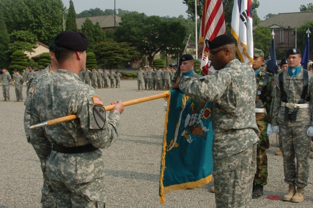 U.S. Troop Command- Korea Command Sgt. Maj. Charles E. Smith unrolls the new flag representing the newly named Troop Command - Special Troops Battalion during the U. S. Army Troop Command deactivation and Special Troops Battalion activation Ceremony held at Knight Field, Yongsan Garrison, South Korea on June 27.