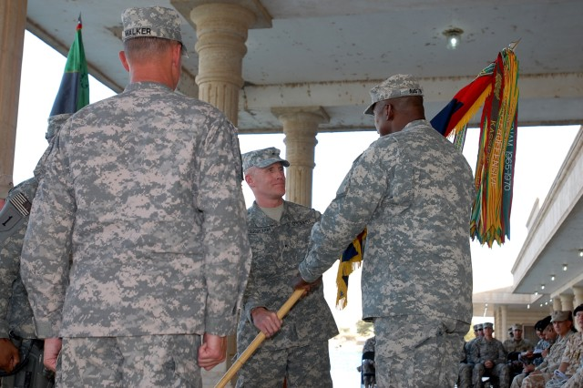 Brig. Gen. James C. Yarbrough passes the Iraq Assistance Group's colors to presiding officer, Lt. Gen. Lloyd J. Austin III, Multi-National Corps - Iraq, commanding general, during the change-of-command ceremony at the Joint Visitor Bureau on Camp Victory Friday.