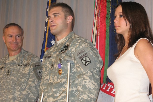 Lt. Gen. David H. Huntoon, Jr., director of the Army Staff, smiles as Capt. Robert Hinchman addresses the audience with his wife Leslie by his side at the Walter Reed Army Medical Center, Friday.