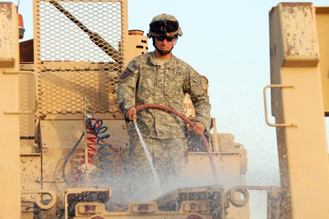 "Pfc. Joshua Gromer, an 88M - motor transport operator, assigned to 2nd Transportation Company, 2nd Transportation Battalion, 4th Sustainment Brigade hoses down an M1070 Heavy Equipment Transport tractor, June 23, 2008, at the 401st Army Field Support Brigade wash racks at Camp Arifjan, Kuwait.  Gromer, from Kissimmee, Fla., had just returned from ""a trip north."""