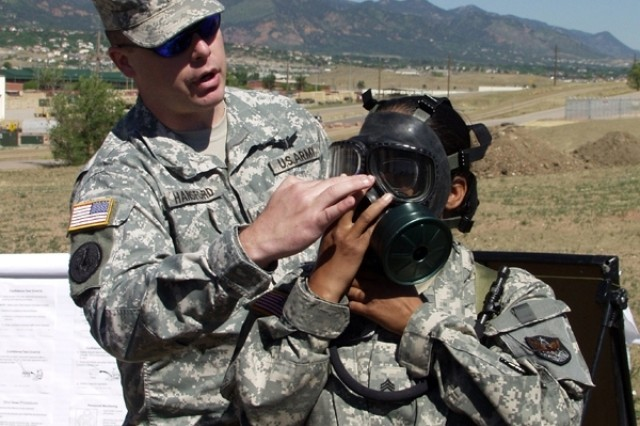 Sgt. 1st Class Jeffrey Hansford, Headquarters and Headquarters Company, 1st Space Brigade, shows Sgt. Tiana Motton from HHC, 1st Space Brigade, how to properly place an M40A1 chemical protective mask over the face prior to entering the gas chamber during a Chemical, Biological, Radiological and Nuclear Training session at Fort Carson's Range 72 on the morning of June 7.