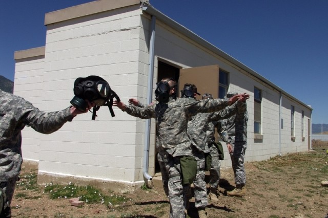 Soldiers from the 1st Space Brigade exit the proper way from a gas chamber at Fort Carson's Range 72 on the morning of June 7, signaling the completion of their mandatory Chemical, Biological, Radiological and Nuclear training.