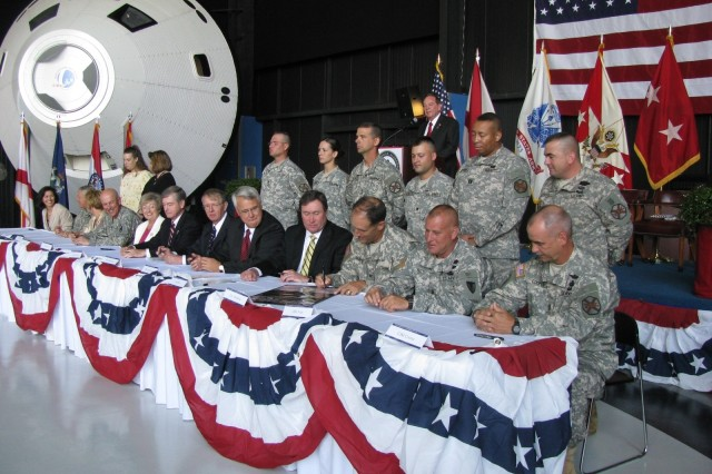Garrison commander Col. John Olsheski, third from right, signs the Army Community Covenant while other signees wait their turn to make official the community's support of the Army during a covenant signing ceremony at the U.S. Space & Rocket Center on June 25, which was part of  Armed Forces Celebration Week. At the signing table with Olshefski are, from far left, Irma Tuder of the Huntsville/Madison County Chamber of Commerce, Army vice chief of staff Gen. Richard Cody, waiting spouse and Missile Defense Agency employee Gabriel Wiley, Redstone Arsenal and AMCOM commander Maj. Gen. Jim Myles, Huntsville Mayor Loretta Spencer, Madison County Commission Chairman Mike Gillespie, Madison Mayor Sandy Kirkindall, State of Alabama representative Bruce Anderson, community leader Joe Ritch, AMCOM Command Sgt. Maj. Ricky Yates and Garrison Command Sgt. Maj. Rickey Cooper. Standing behind them are Redstone Arsenal Soldiers, waiting spouses and, at the podium, retired Brig. Gen. Larry Capps.