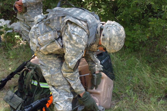 Boosier City, La. native Pvt. Tim Dowings, Company E, 2nd Battalion, 8th Cavalry Regiment, 1st Brigade Combat Team, 1st Cavalry Division fills his canteens with water during dismounted training at Fort Hood, Texas June 26. ""