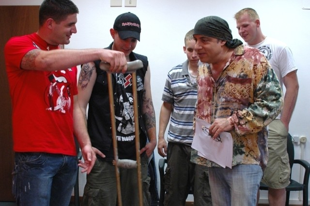 Sgt. Justin Varnes (left), a Warrior Transition Soldier from Vicenza, Italy, presents a crutch that he and fellow WTU Soldiers Pfc. Christopher Gross, Spc. Max Kenworthy and Spc. Carl Vandenberg signed for Steve Van Zandt. The Soldiers met with Van Zant prior to the guitarist taking the stage with Bruce Springsteen and E Street Band in Milan, Italy, June 25. The Soldiers were invited to the concert as guests of Van Zant.