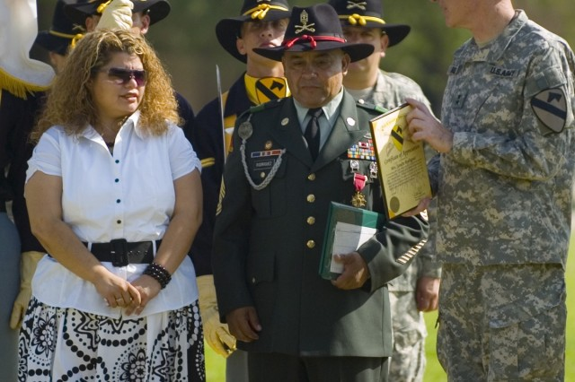 After awarding the Legion of Merit to Del Rio, Texas native 1st Sgt. Agustin Rodriguez (center), who recently served as the rear detachment command sergeant major for the 2nd Brigade Combat Team, 1st Cavalry Division, Maj. Gen. Daniel P. Bolger (right), commanding general, 1st Cav. Div., prepares to award his wife Sandra Rodriguez with a certificate of appreciation during the 1st Cav. Div.'s Distinguished Service and Welcome Ceremony July 1 at Fort Hood, Texas for her support during 1st Sgt. Rodriguez's career. Rodriguez served on active duty for 26 years and will be retiring to central Texas with his family.