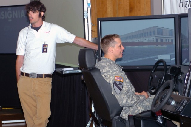 Brian Beldyga (left), tour manager and event facilitator for the 'Save A Life Tour' addresses an audience about the way the program's multi-million dollar drunk driving simulator mimics the effects of impaired driving while Scotsdale, Ariz. native Spc. Shane Sebastian, a light-wheeled vehicle mechanic for Headquarters Support Company, Division Special Troops Battalion, sits awaiting his turn on the simulator June 27 at Fort Hood, Texas.