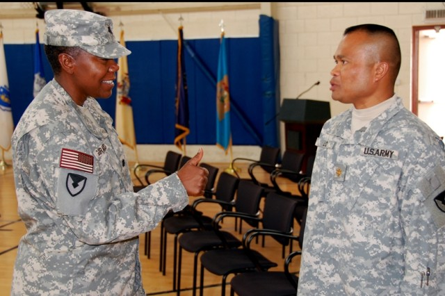 """Lt. Col. Maxine C. Girard, outgoing commander, 1st Battalion, 401st Army Field Support Brigade gives Maj. Inh E. Lo, battalion executive officer, a """"thumbs up"""" following the just-completed change of command ceremony at which she relinquished command to Lt. Col. Jerry Jones, at Camp As Sayliyah, Qatar, June 30.  Lo was the commander of troops for the ceremony, which saw the battalion's colors and responsibilities passed to Jones."""