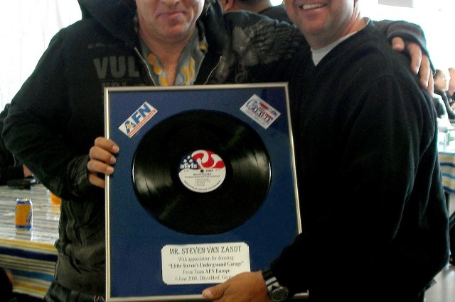 """AFN Europe Commander Col. Scott Malcom presents a token of AFN's appreciation to Steven Van Zandt. It's an AFRTS disc of the Bruce Springsteen and the E Street Band's """"Born in the USA"""" album.  Below it is a plaque thanking Van Zandt for donating """"Little Steven's Underground Garage"""" to American Forces Network Europe. The show airs on AFN The Eagle Saturdays 4-6 p.m. Central European Time. ( Photo courtesy of Col. Scott Malcom)"""