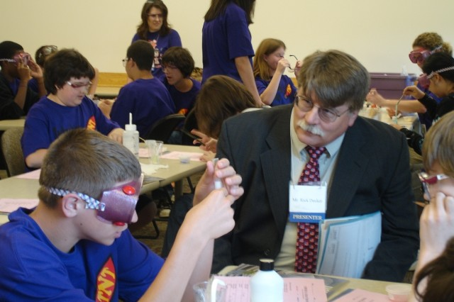 """ECBC Technical Director Rick Decker observes the Aca,!A""""Chemical Reactions SleuthAca,!A? presentation as students from Aberdeen Middle School demonstrate what they learned during the Technology Needs Teens event May 28."""