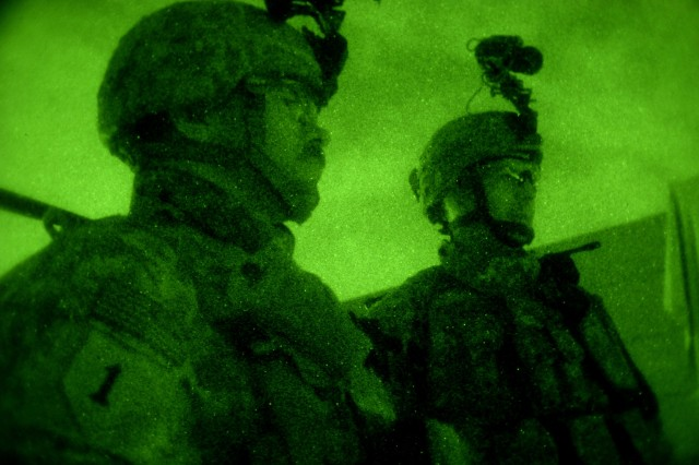Army Maj. John Atilano and Maj. Scott Hedberg, both from 2nd Tank Battalion, 34th Armor Brigade, 9th Iraqi army division (mechanized) Military Transition Team, observe Iraqi army soldiers receiving night vision familiarization at a check point near Camp Taji, Iraq, March 31, 2008.  Majors who serve 12 months on any transition team will be considered to have met the key developmental career requirements for their branch.