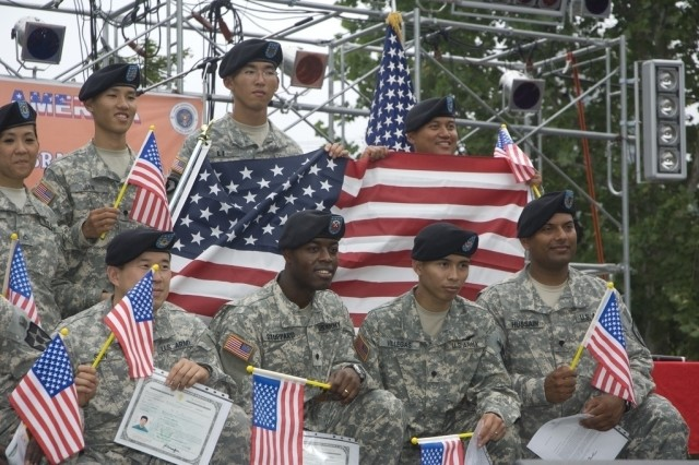 The newest U.S. citizens pose with U.S. flags after the USAG-Yongsan July 4 Naturalization Ceremony.