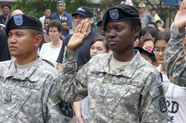 Pvt. 1st Class Kimberly Miranda (right) born and raised in the Central American country of Belize, takes the oath of allegiance July 4 to become a U.S. citizen.