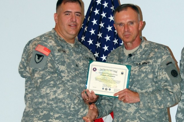 Sgt. Robert D. Ritchie receives his Operation Freedom Strong Certificate of Reenlistment from Lt. Gen. James J. Lovelace, commanding general, Third Army/U.S. Army Central, at Camp Arifjan, Kuwait, July 4, 2008.  Ritchie, an Army reservist, is assigned to Detachment 9, Multifunctional Support Command, which is currently augmenting the 401st Army Field Support Brigade. Ritchie and 18 other Soldiers had just participated in a group reenlistment ceremony where Lovelace administered the Oath of Enlistment.