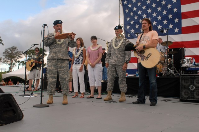 Maj. Gen. Raymond V. Mason, 8th Theater Sustainment Command commanding general, presented a commemorative plaque to Billy Ray Cyrus for his participation in the Army Community Covenant signing and performance at the 37th Annual 4th of July Spectacular on Sills Field, Schofield Barracks. (Photo by Sgt. David House)