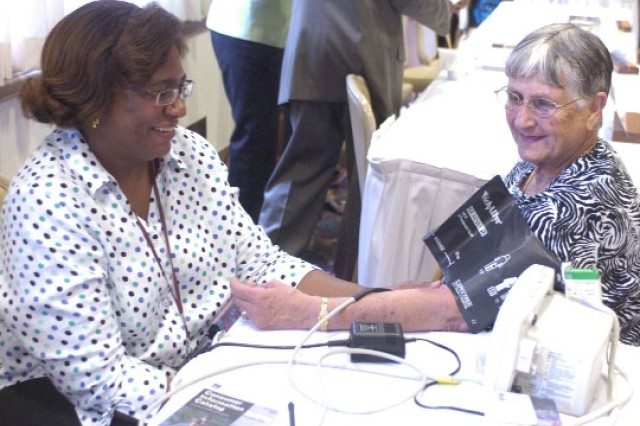 Georgia Crawford (left), a registered nurse from the Lawrence Joel Army Health Clinic's Community Health, checks Eleanor Kensinger's blood pressure.