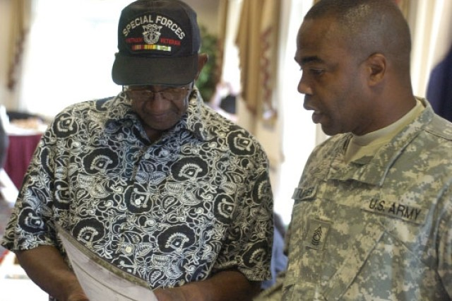 Master Sgt. Ira Turner (right), from Human Resource Command, Alexandria, Va., explains the Combat Related Special Compensation program to Master Sgt. (Ret.) Alexander Jones from Decatur. Turner's was one of more than 20 booths set up to provide information to the retirees.