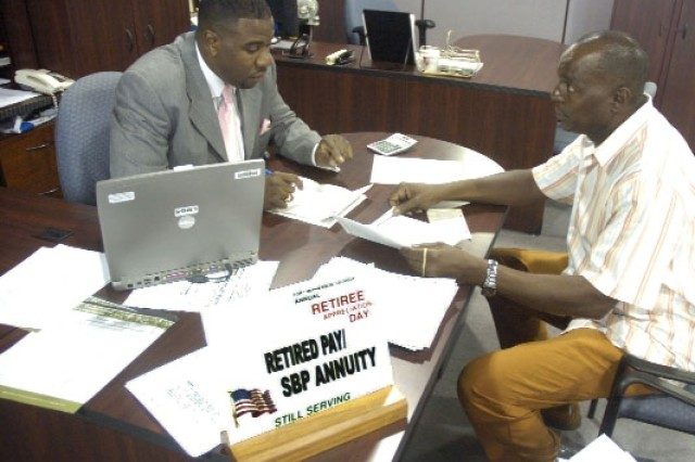 Earl Roberts (left), from the Defense Finance and Accounting System in Cleveland, Ohio, assists Staff Sgt. (Ret.) Wallace Strickland with a retirement pay issue.   Strickland, a 20-year veteran from Rockmart, took advantage of the various opportunities to clarify available benefits.