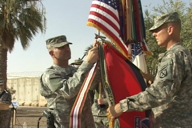 Maj. Gen. Michael Oates, Multi-National Division -- Center commander, and Command Sgt. Maj. James Redmore place the Afghanistan Campaign Ribbon on the 10th Mountain Division Guidon during a patch cermony July 4 on Camp Victory. The division served in Afghanistan from Jan. 2006-Jan. 2007.