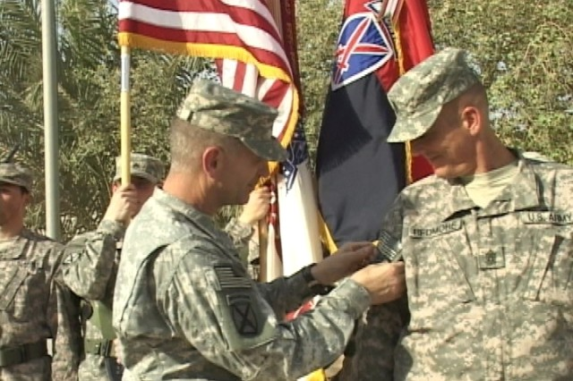 Maj. Gen. Michael Oates, commander of Multi-National Division -- Center, places a combat patch upon the right arm of Command Sgt. Maj. James Redmore during a patch ceremony at Camp Victory July 4.