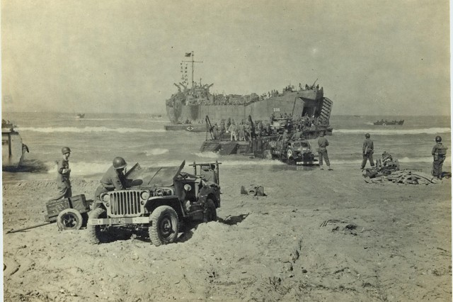 LST landing on beach in Sicily, Italy. Army vehicles unload from LST 338 during the invasion of Sicily, July 1943 (WWII Signal Corps Photograph Collection).