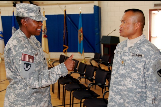 """Lt. Col. Maxine C. Girard, outgoing commander, 1st Battalion, 401st Army Field Support Brigade gives Maj. Inh E. Lo, battalion executive officer, a """"thumbs up"""" following the just-completed change of command ceremony where she relinquished command to Lt. Col. Jerry Jones, at Camp As Sayliyah, Qatar, June 30, 2008.  Lo was the commander of troops for the ceremony, which saw the battalion's colors and responsibilities passed to Jones."""