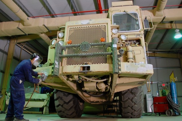 Nayas Thulung, an employee with ITT Corp., sands the front bumper of a Caterpillar 621B Scraper, June 29, at the 1st Battalion, 401st Army Field Support Brigade Auto Body Repair Facility at Camp As Sayliyah, Qatar. Since the facility opened Apr. 17, approximately 50 Humvees, 7 scrapers, and other assorted items of equipment have had body work done by the ABRF staff.