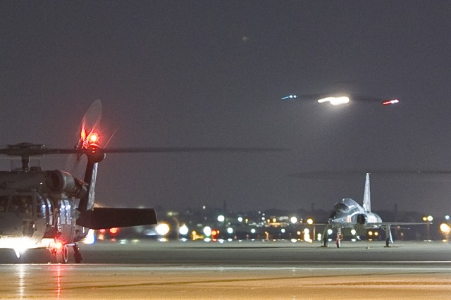 """Black Hawk helicopters from the Texas Army National Guard wait with their engines running as the C-17 Globemaster III aircraft carrying three former hostages approaches Lackland Air Force Base, Texas, July 2, 2008. Three U.S. government contractors were rescued by Colombian security forces after being held captive by the Revolutionary Armed Forces of Columbia, or FARC, since their plane crashed in a remote area in February 2003. <a href=""""http://www.army.mil/-news/2008/07/05/10652-public-statement-by-marc-gonsalves-thomas-howes-and-keith-stansell/index.html"""">click for more</a>"""