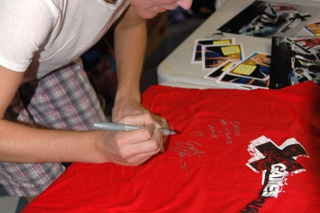 Grete Eliassen, X-Game athlete, signs a shirt for a fan at the Morale, Welfare and Recreation clamshell on Bagram Air Field, Afghanistan, June 28. Eliassen, Danny Kass and Nate Holland visited BAF on a morale tour but wound up getting their own taste of extreme living when they experienced the life of a servicemember -- Bagram style.