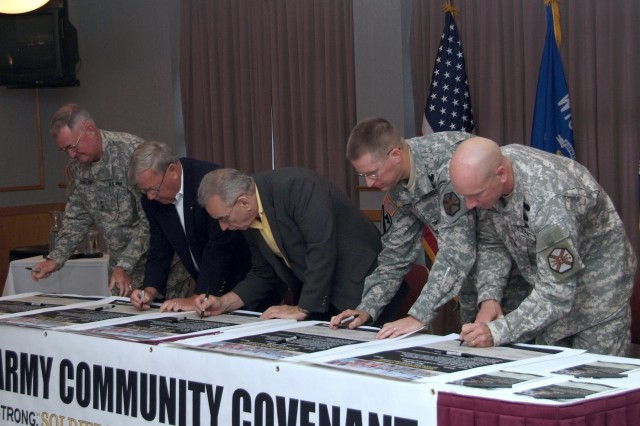 Fort McCoy leadership and the mayors of the neighboring cities of Tomah and Sparta, Wis., put pens to paper as they sign the Army Community Covenant July 2 at Fort McCoy.  Pictured left to right are Fort McCoy Senior Mission Commander Maj. Gen. James R. Sholar, Sparta Mayor John Sund, Tomah Mayor Ed Thompson, Fort McCoy Garrison Commander Col. David E. Chesser and Fort McCoy Garrison Command Sergeant Major Command Sgt. Maj. Matthew K. Dubois.