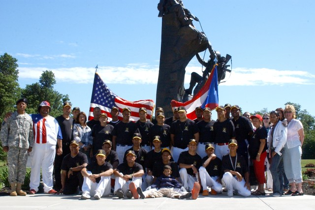 From left, Command Sgt. Maj. Terry Parham, division rear command sergeant major, and Eric Caraballo, owner and coach of a baseball team from Puerto Rico, stand with team members, family members, chaperones and local hosts Thursday at Memorial Park. The team stayed in the area for 12 days to play baseball and interact with people of other cultures.