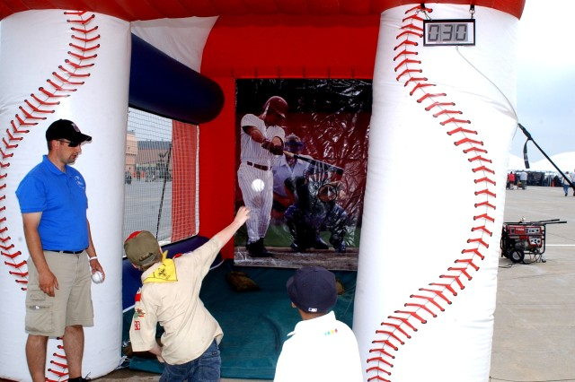 Children try out the baseball fastpitch game during Mountainfest.