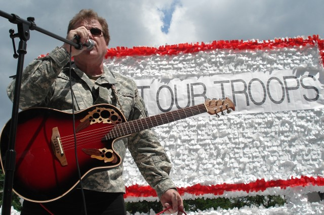 Barrington, IL Rock Musician, Joe Cantafio, lead singer of the '101st Rock Division' band, performs for the crowd with patriotic music on a float with Soldiers, Marines, Airman and Coast Guard, at the Hinsdale, IL 2008  4th of July parade, to a crowd of about 10,000.